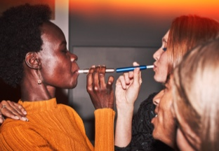 A woman holding an IQOS device with friends at a party.